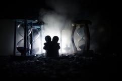 temps et concept d'amour Les silhouettes des chiffres en céramique de jouet étreignant entre les sabliers dans l'obscurité ont al Image libre de droits