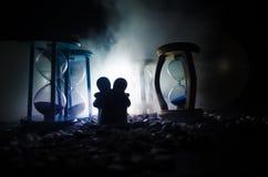 temps et concept d'amour Les silhouettes des chiffres en céramique de jouet étreignant entre les sabliers dans l'obscurité ont al Image stock