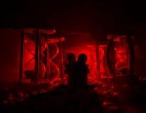 temps et concept d'amour Les silhouettes des chiffres en céramique de jouet étreignant entre les sabliers dans l'obscurité ont al Photo libre de droits