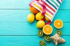 Temps et fruits d'amusement d'été sur le fond en bois bleu Moquerie haute et pittoresque Orange, citron, kiwis dans le sac et coq Photos libres de droits