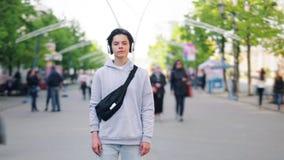 Temps-faute d'adolescent écoutant la musique dans des écouteurs se tenant dans la ville banque de vidéos
