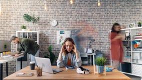 Temps-faute de la fille soumise à une contrainte s'asseyant au bureau touchant la tête quand déplacement de collègues banque de vidéos