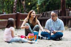 Temps heureux d'amusement de dépense de famille jouant ensemble en sable Image stock