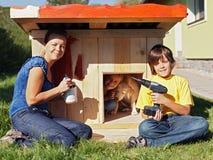 Temps heureux de famille - fabrication d'un abri pour notre chiot Photos stock