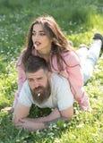 Temps insouciant ensemble Couples dans l'amour sur extérieur ensoleillé Femme se trouvant sur l'homme avec des fleurs dans les bo Photos stock