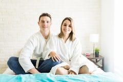 Temps libre de dépense de couples sur le lit à la maison images stock
