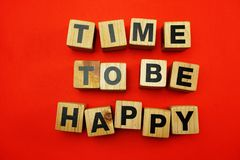 Temps pour être heureux créé avec des lettres d'alphabet de cubes sur le fond rouge photos stock