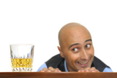 Temptation. Businessman looking at a glass of alcohol isolated in white Royalty Free Stock Images
