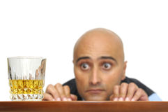 Temptation. Businessman looking at a glass of alcohol isolated in white Stock Image