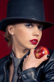 Temptation. Sensual blond girl wearing a hat, offering an apple Royalty Free Stock Photo