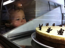Temptation. Little kid looking at cake with temptation royalty free stock photography