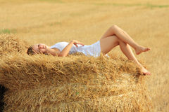 Temptation. Young attractive barefoot girl lying on a bale of yellow straw at field Stock Photography