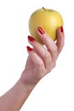 Temptation. Women's beautiful hand with red manicure holding yellow apple isolated on white background Royalty Free Stock Photos
