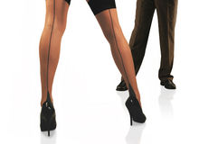 Temptation legs. Woman's legs in thigh high stockings in front man in slacks Stock Photography