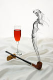 Temptation Series. Wooden pipe and wine glass on satin with drifting smoke in the shape of a beautiful woman Royalty Free Stock Photo
