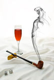 Temptation Series. Wooden pipe, dice, and wine glass on satin with drifting smoke in the shape of a beautiful woman Royalty Free Stock Photography
