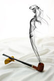 Temptation Series. Wooden pipe on satin with drifting smoke in the shape of a beautiful woman Stock Images