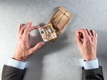 Tempted businessman hands taking a bank note for investment question Royalty Free Stock Image