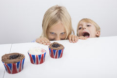 Tempted children looking at cupcakes on table Royalty Free Stock Photos