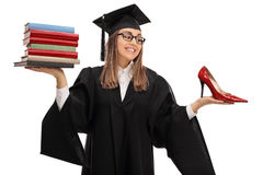 Tempted graduate student holding stack of books and shoe Stock Image