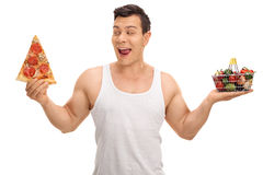 Tempted guy holding pizza slice and small shopping basket. Tempted guy holding a pizza slice and a small shopping basket full of fruits and vegetables isolated stock photo