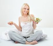 Tempted young woman making a food choice Royalty Free Stock Image