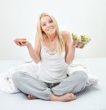 Tempted young woman making a food choice Stock Images