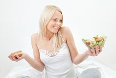 Tempted young woman making a food choice. Between salad and donut royalty free stock photo