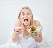 Tempted young woman making a food choice Royalty Free Stock Photography