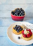 Tempting fruit desserts on a blue plank table. Tempting fruit desserts include juicy fresh blueberries, blueberry butter cake and chocolate raspberry tart with Royalty Free Stock Images