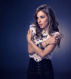 Tempting. A model female dressed in a Polka Dot blouse, denim shorts, wearing fancy pearl ring, dark color necklace and fashionable bangles on isolated dark blue stock photos