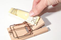 Tempting!. Mousetrap with 200-Euro-Note and fingers pulling Stock Images
