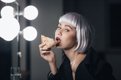 Tempting woman in blonde wig eating pizza and drinking champagne. Tempting tender young woman in blonde wig eating pizza and drinking champagne sitting near the Stock Photos