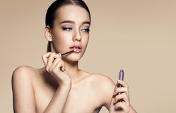 Tempting young woman with lip gloss Stock Photo