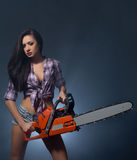 Tempting young woman posing with chainsaw Stock Images