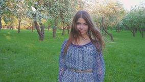 Tempting young woman walking in an apple orchard in the spring flowers white. Portrait of a beautiful girl in the stock video footage