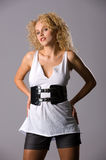 Temptress. A young beautiful blonde with curly hair, in short shorts and white T-shirt Stock Image