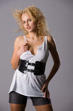 Temptress. A young beautiful blonde with curly hair, in short shorts and white T-shirt Royalty Free Stock Photo