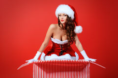 Temptress santa. Beautiful young woman in Santa Claus costume posing with a huge gift box over red background. Christmas Royalty Free Stock Photo