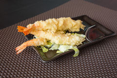 Tempura shrimps. Japanese Cuisine,Tempura Shrimps Deep Fried Shrimps with sauce and vegetables on a black plate. Brown background,shallow depth of field stock photography