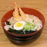 Tempura udon with fried shrimps, boiled egg, green algae, leeks, tipical japanese noodles. Tempura udon with fried shrimps, boiled egg, green algae, leeks stock image