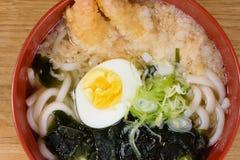 Tempura udon with fried shrimps, boiled egg, green algae, leeks, tipical japanese noodles. Tempura udon with fried shrimps, boiled egg, green algae, leeks stock images