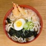 Tempura udon with fried shrimps, boiled egg, green algae, leeks, tipical japanese noodles. Tempura udon with fried shrimps, boiled egg, green algae, leeks stock photos