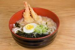 Tempura udon with fried shrimps, boiled egg, green algae, leeks, tipical japanese noodles. Tempura udon with fried shrimps, boiled egg, green algae, leeks stock photography