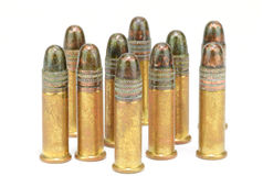Ten .22 caliber rifle rounds, standing, on white Stock Images