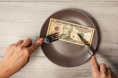Ten American dollars bill on brawn plate and male hands with for. K and knife. Money ready to be eaten. Concept of financial relationships Royalty Free Stock Photo