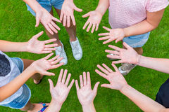 Ten arms of children in circle with palms of hands up Stock Photos