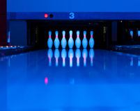 Ten bowling pins at the end of alley. Ultraviolet luminosity Royalty Free Stock Image