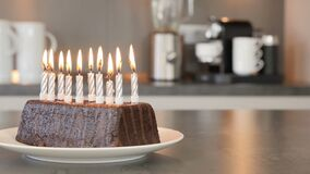 Ten candles on a birthday cake burning down to be blown out in a modern kitchen stock video footage
