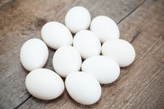 Ten chicken white eggs are on wooden floor Royalty Free Stock Photography